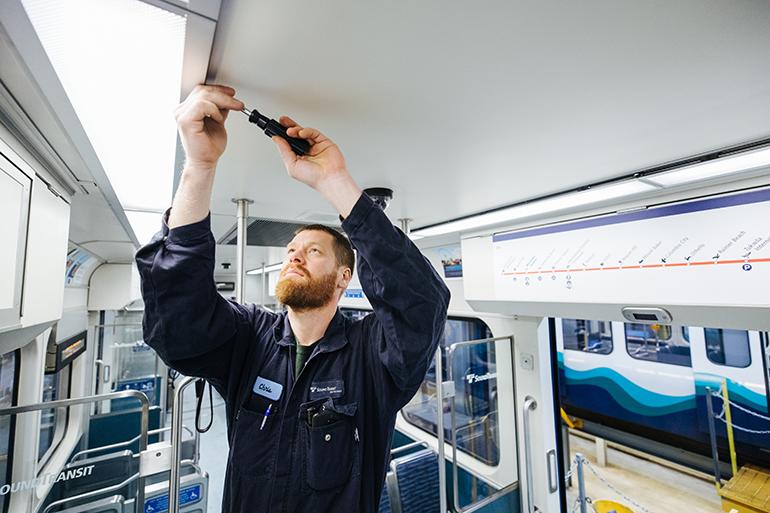 Un trabajador le da mantenimiento a un tren de Link light rail en la Unidad de Operaciones y Mantenimiento en Seattle. El trabajador está en el interior del tren reparando el sistema de iluminación del plafón con un desarmador.