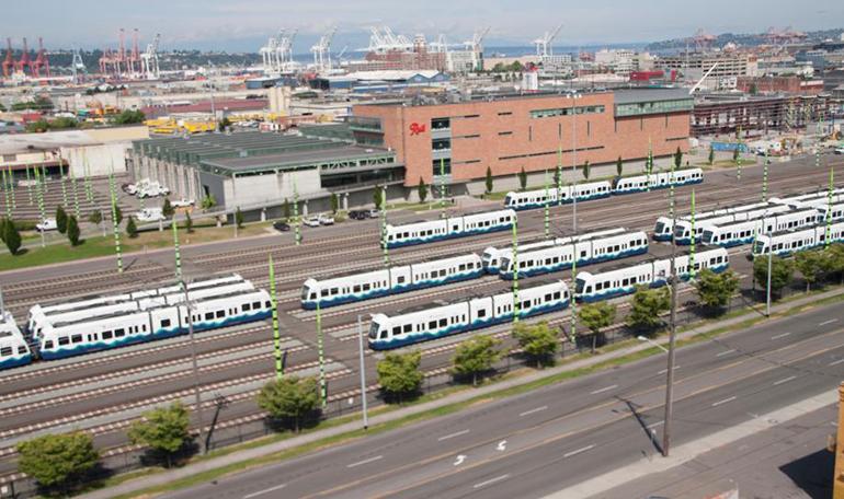 Vista aérea de la Unidad de Operaciones y Mantenimiento actual en Seattle. Esta unidad recibe, almacena y da servicio a los trenes de Link light rail de Sound Transit. El sitio incluye un edificio de almacenamiento para trenes de Link, oficinas para operaciones y controles, y un patio con los trenes de Link formados en las vías.